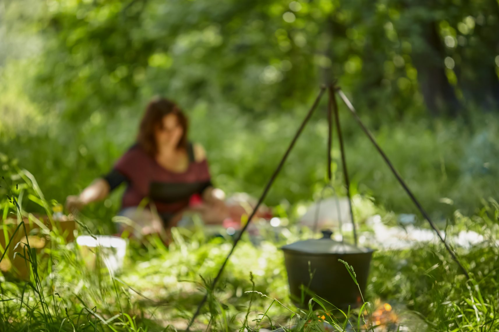 Defocused picnic background. Blurred background woman and bowler hat on fire in summer forest. Cooking food in a pot on a fire in nature. Cooking in nature
